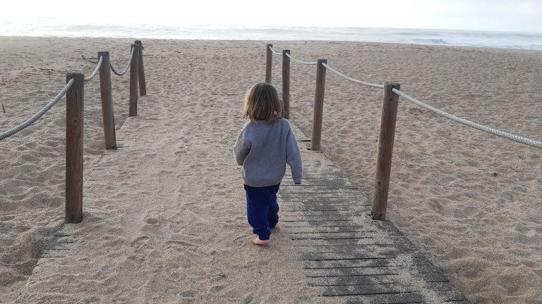menino caminhando para a praia